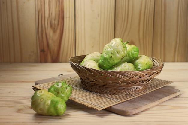 Panier d'osier aux fruits de noni sur tapis de bambou sur fond en bois
