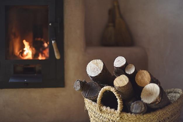 Panier en osier avec bois de chauffage et poêle allumé à la maison