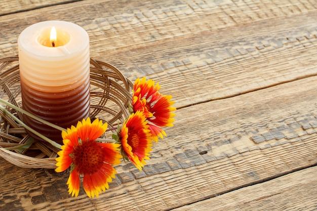 Panier en osier avec bougie allumée et fleurs sur planches de bois. vue de dessus. notion de vacances.