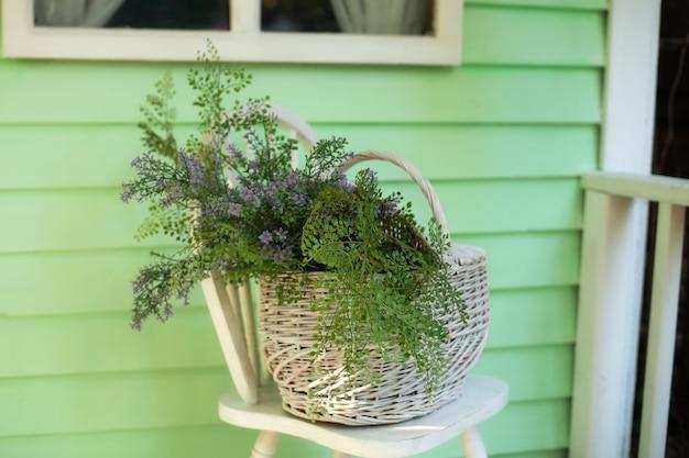Panier en osier avec bouquet de fleurs sauvages sur une chaise près du mur décor d'automne élégant sur le porche de la maison