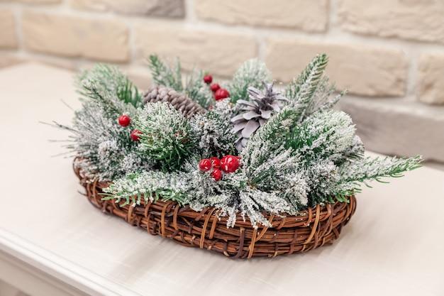 Panier en osier closeup nouvel an avec des branches de conifères épinette recouvertes de neige, baies de cônes rouges. décor de noël, décoration de table, fait à la main