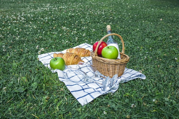 Panier en osier avec croissants, pommes et bouteille de vin rosé