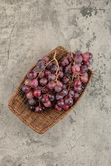 Panier en osier de délicieux raisins rouges sur table en marbre.