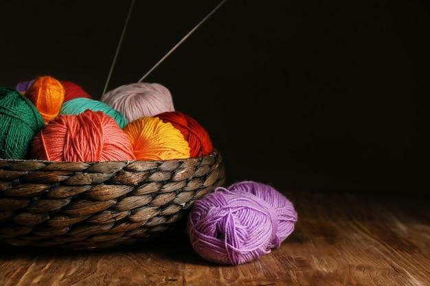 Panier en osier avec du fil à tricoter sur une table en bois contre une surface sombre