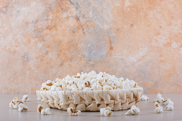 Panier en osier de maïs soufflé salé pour soirée cinéma sur fond blanc. photo de haute qualité
