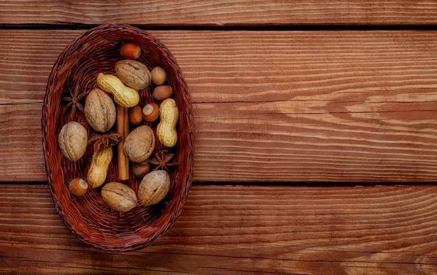 Panier en osier avec noisette, noix, arachide et épices sur fond en bois texturé. haut de la vue.