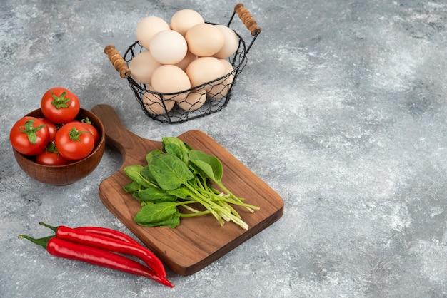Panier en osier d'oeufs biologiques crus et légumes frais sur marbre.