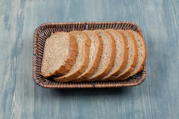 Panier en osier de pain de seigle tranché sur table en pierre.