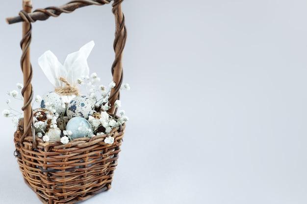 Panier en osier de pâques plein de petits œufs tachetés décorés de fleurs blanches sur une surface claire.