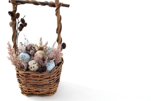 Panier en osier de pâques rempli de petits œufs tachetés décorés d'herbe sèche et pelucheuse.