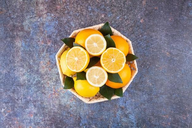 Panier en osier plein de citrons frais avec des feuilles sur marbre.