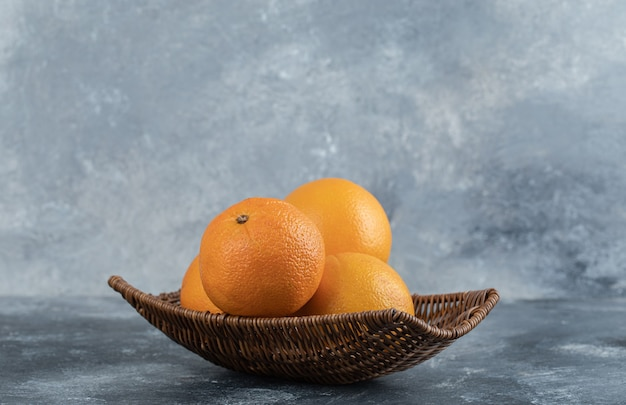 Un panier en osier plein de fruits orange.