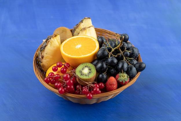 Un panier en osier plein de fruits sur une surface bleue