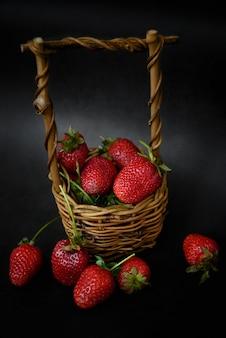 Panier en osier plein de srtawberries mûres rouges sur la nourriture d'été de surface sombre