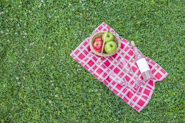 Panier en osier avec des pommes et une bouteille de vin rosé