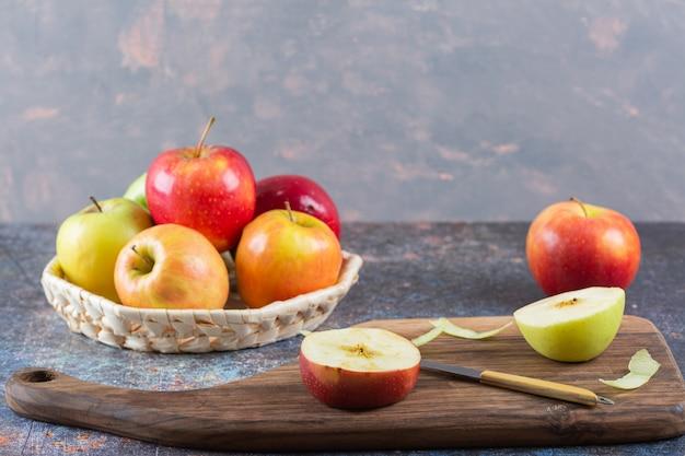 Panier en osier de pommes fraîches colorées sur table en marbre.