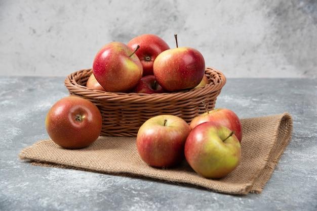 Panier en osier de pommes mûres brillantes sur une surface en marbre.