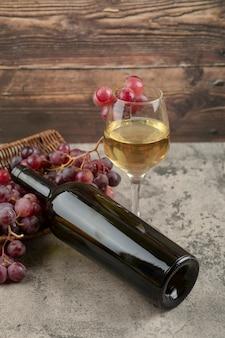 Panier en osier de raisins rouges avec verre de vin blanc sur table en marbre.