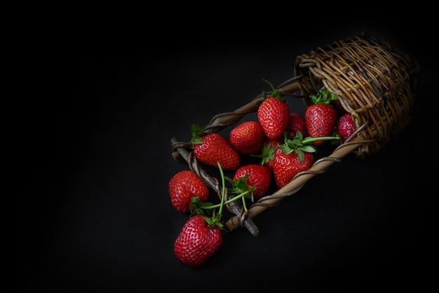 Le panier en osier repose sur une surface sombre pleine de fond de nourriture d'été mûre rouge srtawberries