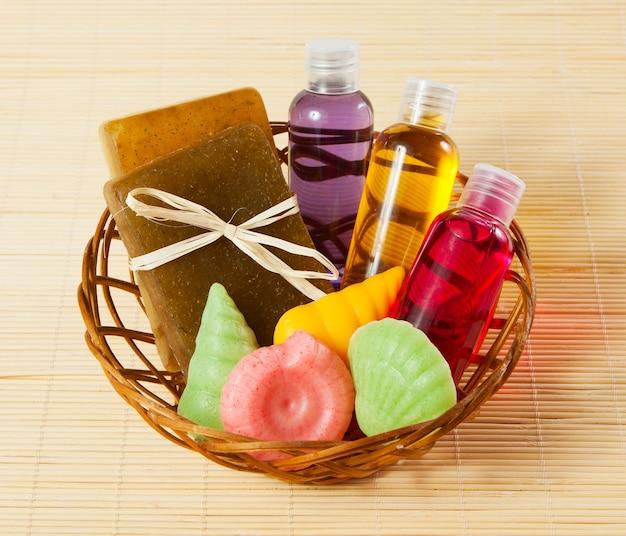 Panier en osier avec savon, gel et autres accessoires de bain et de douche sur tapis de bambou