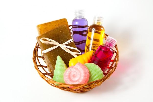 Panier en osier avec savon, gel et autres accessoires pour prendre un bain et une douche sur un fond blanc