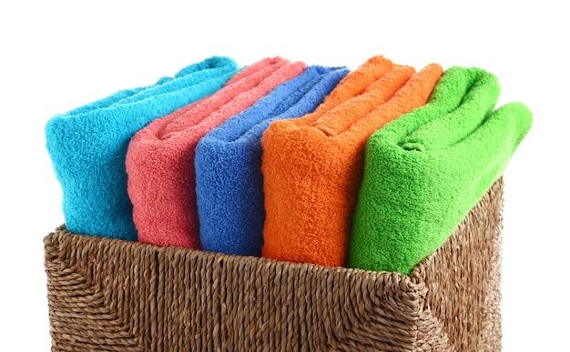 Panier en osier avec serviettes propres pliées sur blanc
