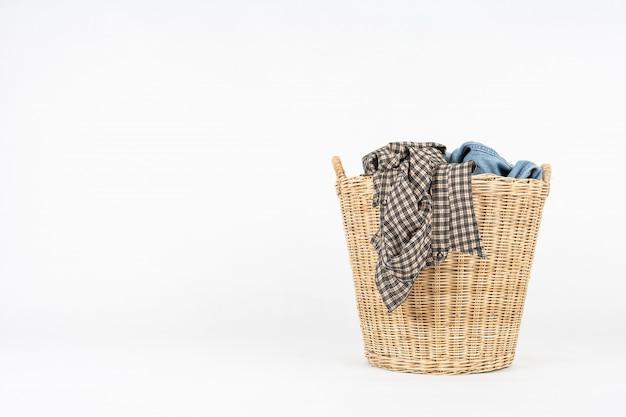 Panier en osier de vêtements isolé sur blanc