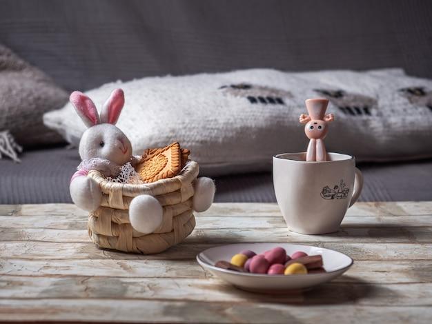 Panier de pâques avec un lièvre et des biscuits et un talelochka avec des œufs en chocolat pour pâques