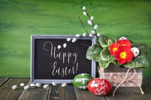 Panier de pâques avec des oeufs de pâques peints et fleur de pot de primevère rouge sur fond en bois rustique, texte