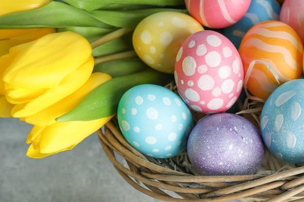 Panier de pâques rempli d'oeufs colorés et de fleurs sur un fond en bois