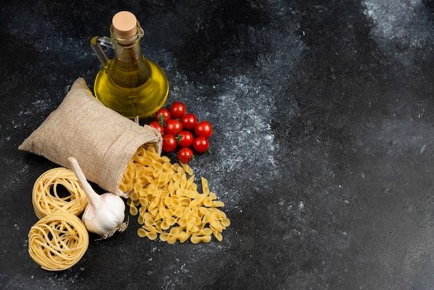 Panier de pâtes avec huile d'olive, tomates cerises et ail autour.