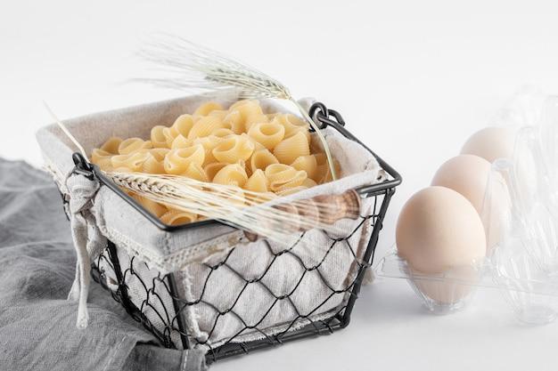Panier de pâtes et œufs crus dans un récipient sur une surface blanche.