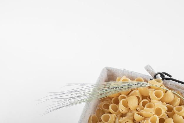 Panier de pâtes sèches avec épi de blé sur blanc.
