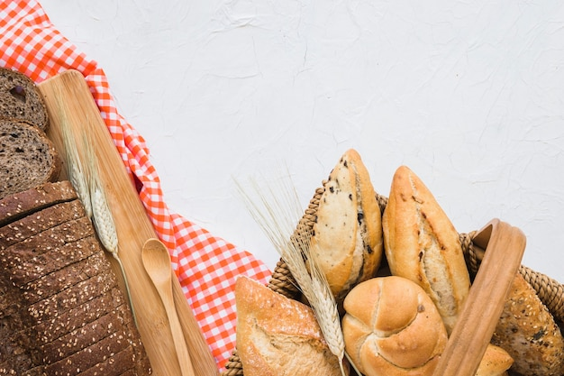Panier avec des petits pains près du pain et du tissu