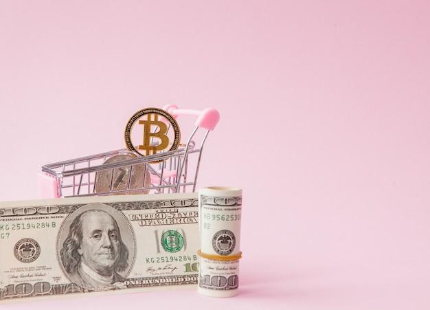 Panier avec pièce de monnaie bitcoin et dollars sur rose
