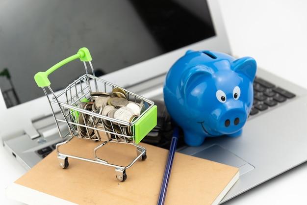 Panier. pièce de monnaie dans le panier avec tirelire et portefeuille sur fond de cahier et ordinateur portable. achats en ligne, économies d'investissement, achat, concept d'entreprise.