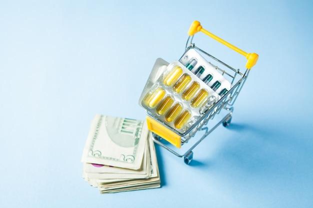 Panier avec des pilules et de l'argent sur une surface bleue