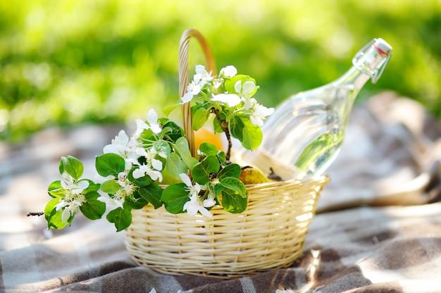 Panier de pique-nique avec des fruits, des fleurs et de l'eau dans la bouteille en verre