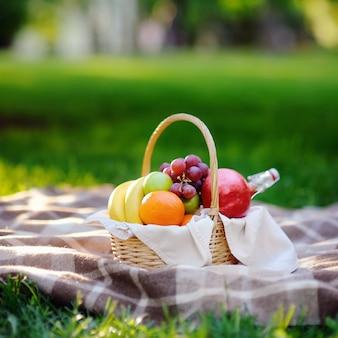 Panier de pique-nique avec des fruits, de la nourriture et de l'eau dans la bouteille en verre