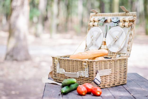 Panier de pique-nique ouvert avec des tomates, des concombres et du pain sur une table en bois dans le parc.