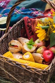 Un panier pique-nique avec pommes, sandwichs et maïs