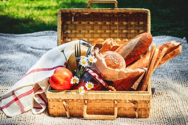 Panier de pique-nique rempli de fruits, pain et pot avec de la confiture d'abricot