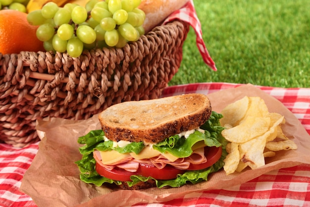 Panier de pique-nique et sandwich au jambon et au fromage