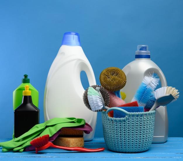 Panier en plastique bleu avec des brosses, des éponges et des gants en caoutchouc pour nettoyer les locaux, à côté d'une bouteille de détergent, fond bleu