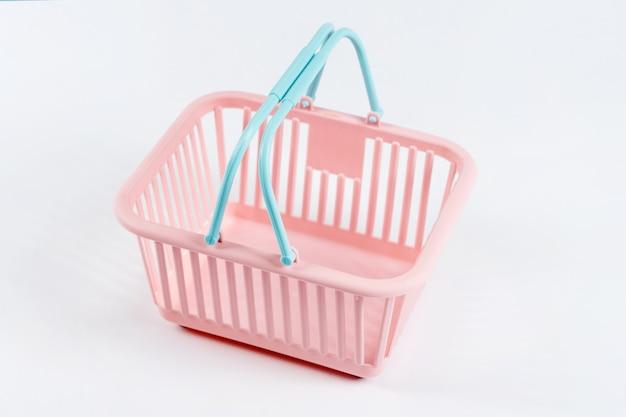 Panier en plastique coloré. panier de supermarché rose et bleu vide sur fond clair. design minimaliste créatif, achats en ligne. concept de vendredi noir et de vente.