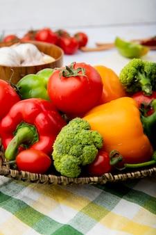 Panier plein de légumes comme des tomates, des poivrons et des oignons verts sur un tissu à carreaux