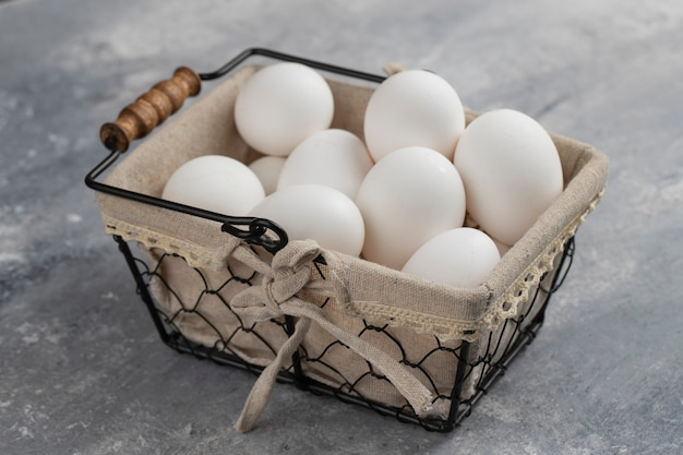 Panier plein d'oeufs de poule blancs frais sur un marbre.