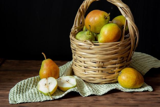 Panier avec des poires sur une table en bois
