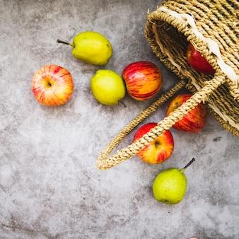 Panier avec des pommes qui tombent