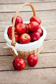 Panier de pommes rouges sur plancher de bois